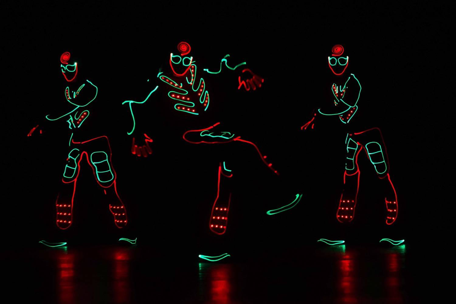 dancers in led suits on dark background, colored show